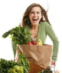A woman carrying a grocery bag of vegetables
