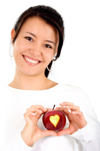 Woman holding an apple with a heart-shaped bite taken out of it