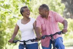 An elderly couple on bicycles laughing together