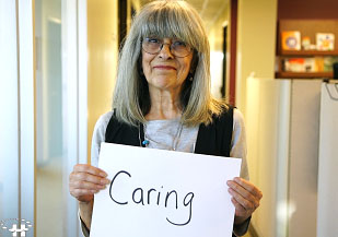 Woman holding sign that says Caring
