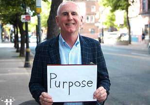 Man holding sign that says Purpose